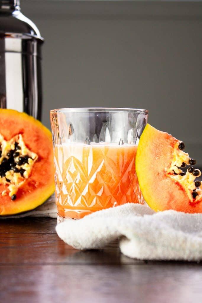 Glass of papaya rum punch beside half a papaya and a papaya slice