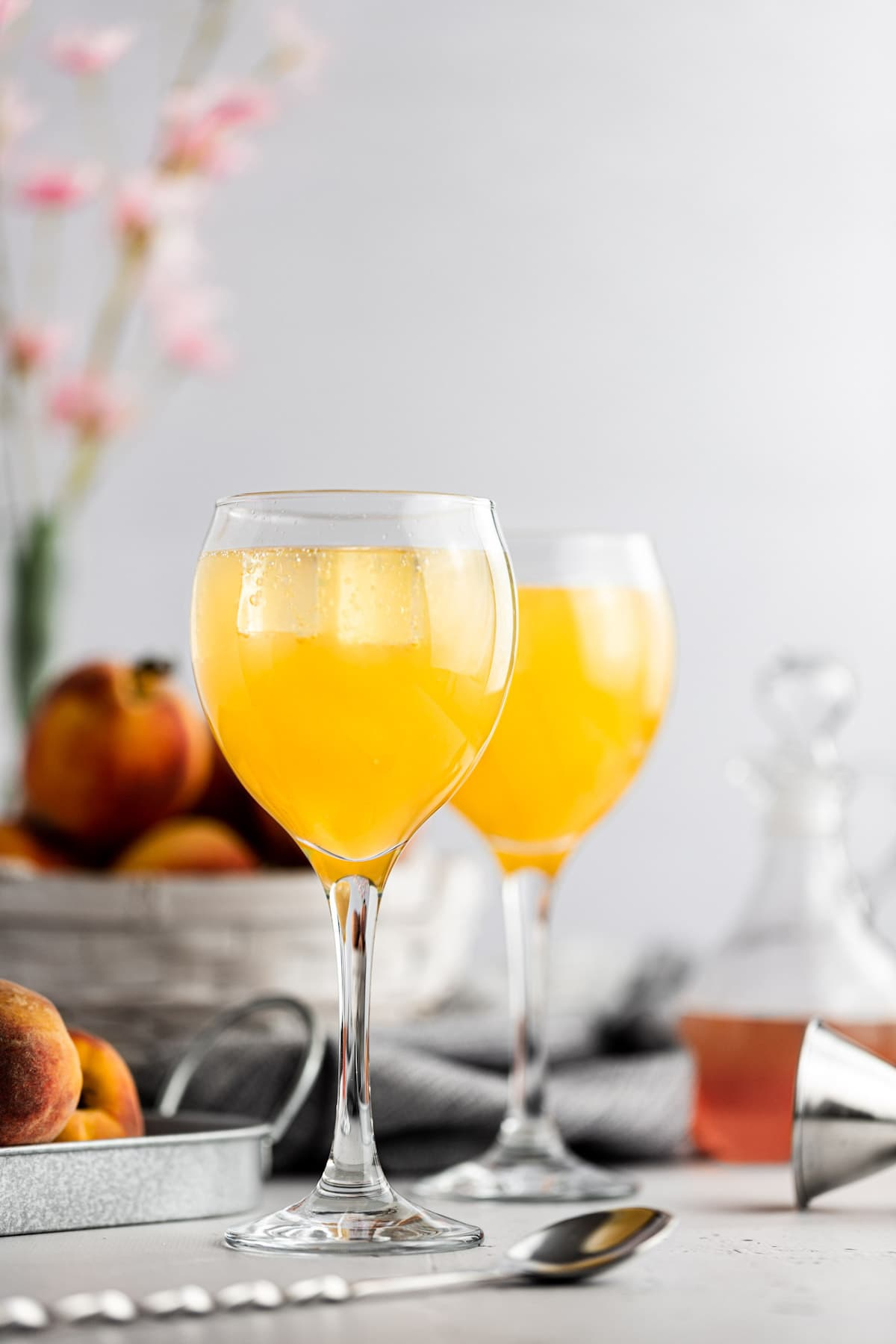 Two peach gin cocktails, next to a basket of fresh peaches, with a grey background.