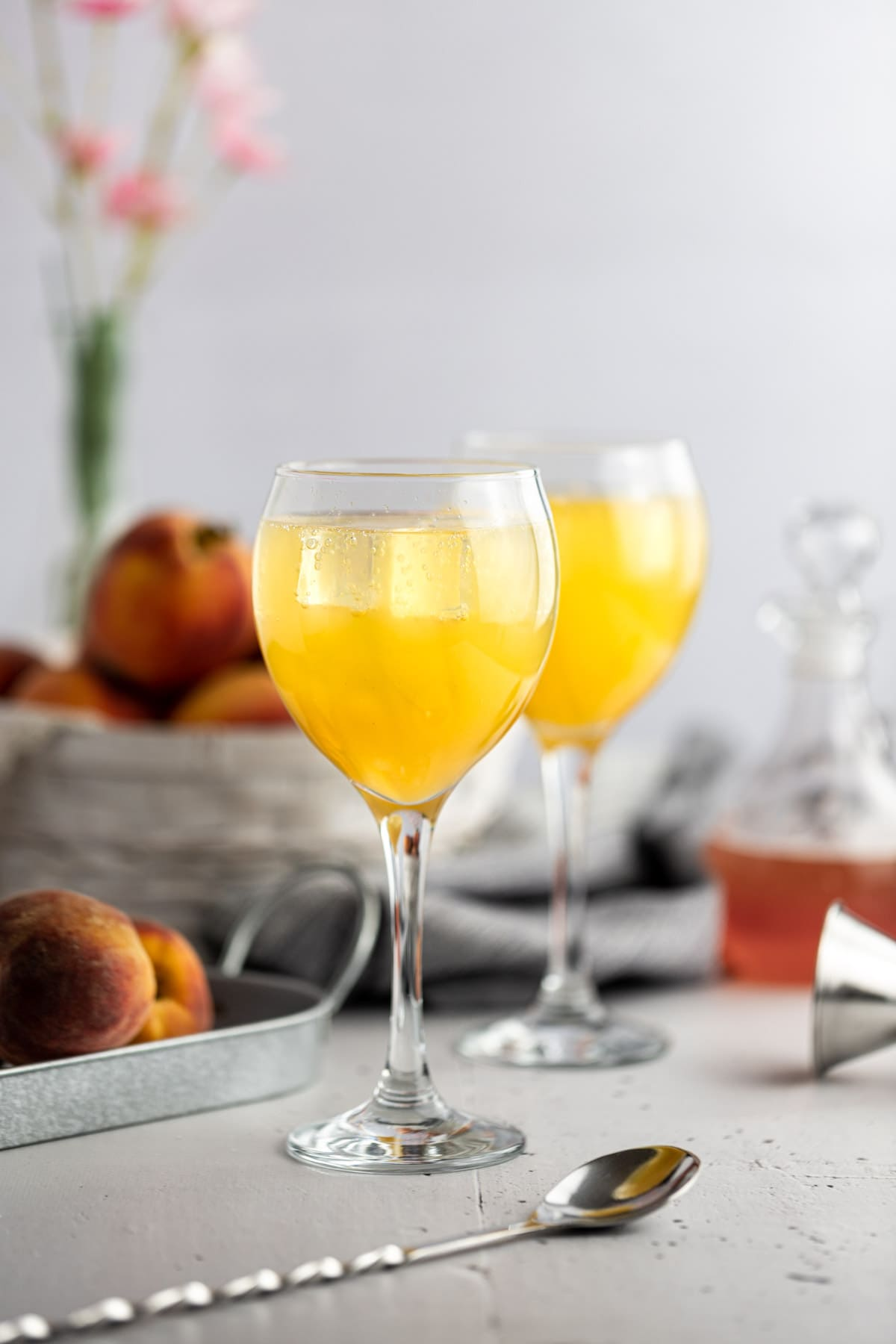 Two peach cocktails on a grey table, next to fresh peaches and a jar of peach syrup.
