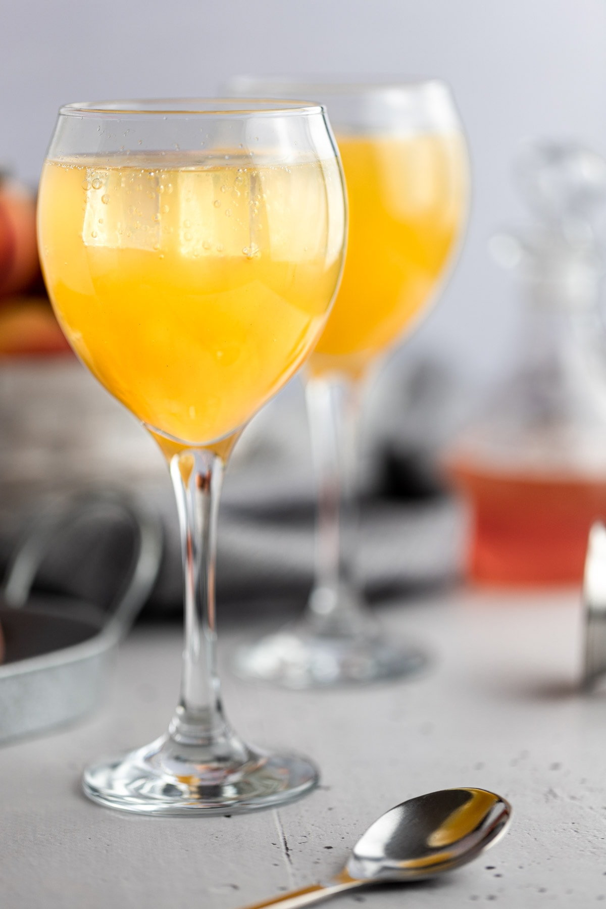 Up close view of an orangey-yellow gin peach cocktail, next to a spoon and fresh peaches with a grey background.