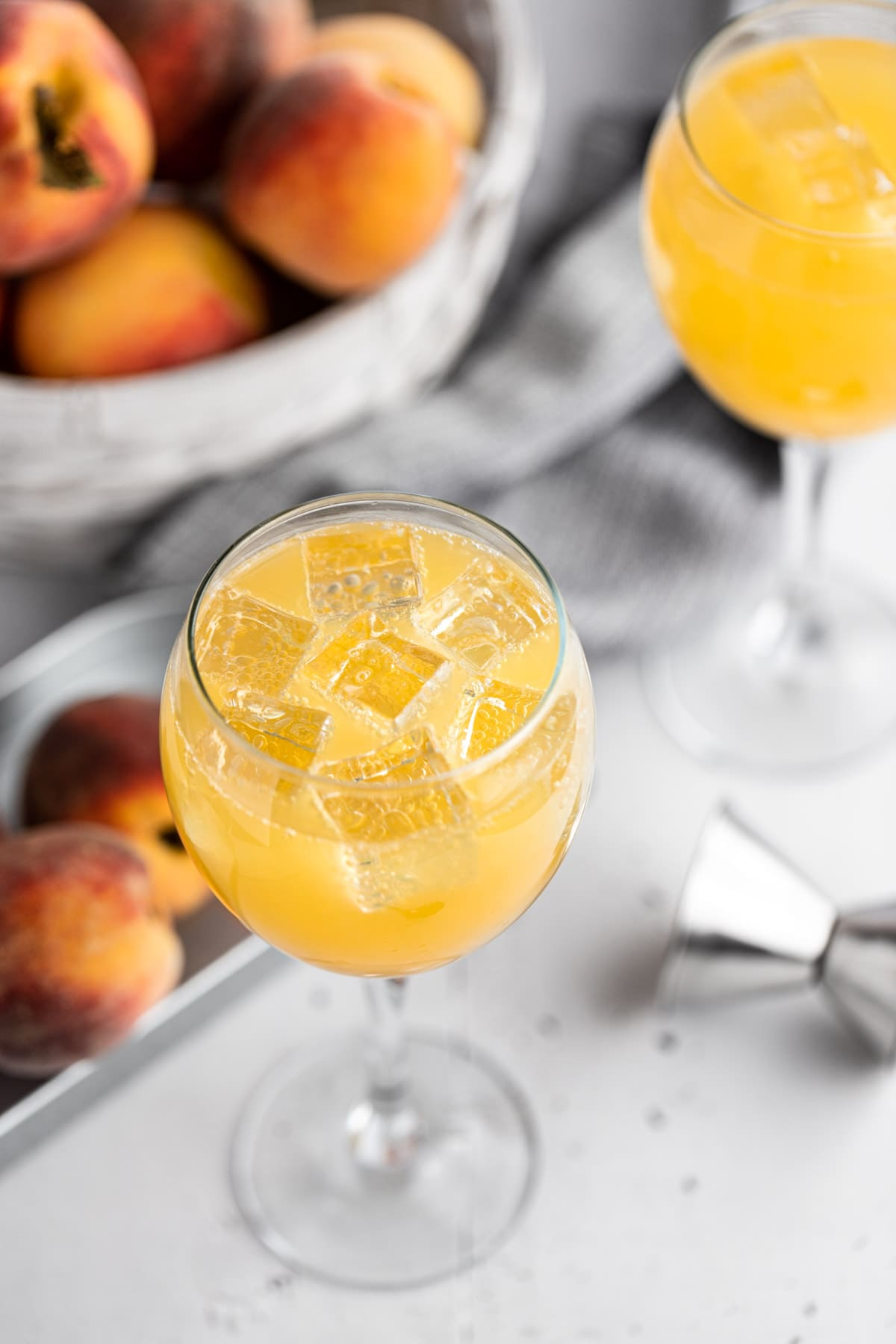 Overhead view of a peach gin cocktail with ice cubes, on a light grey table, next to a metal jigger and metal tin filled with fresh peaches.