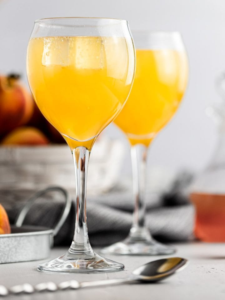 Two peach gin cocktails, next to a metal spoon, with a white basked filled with fresh peaches in the background.