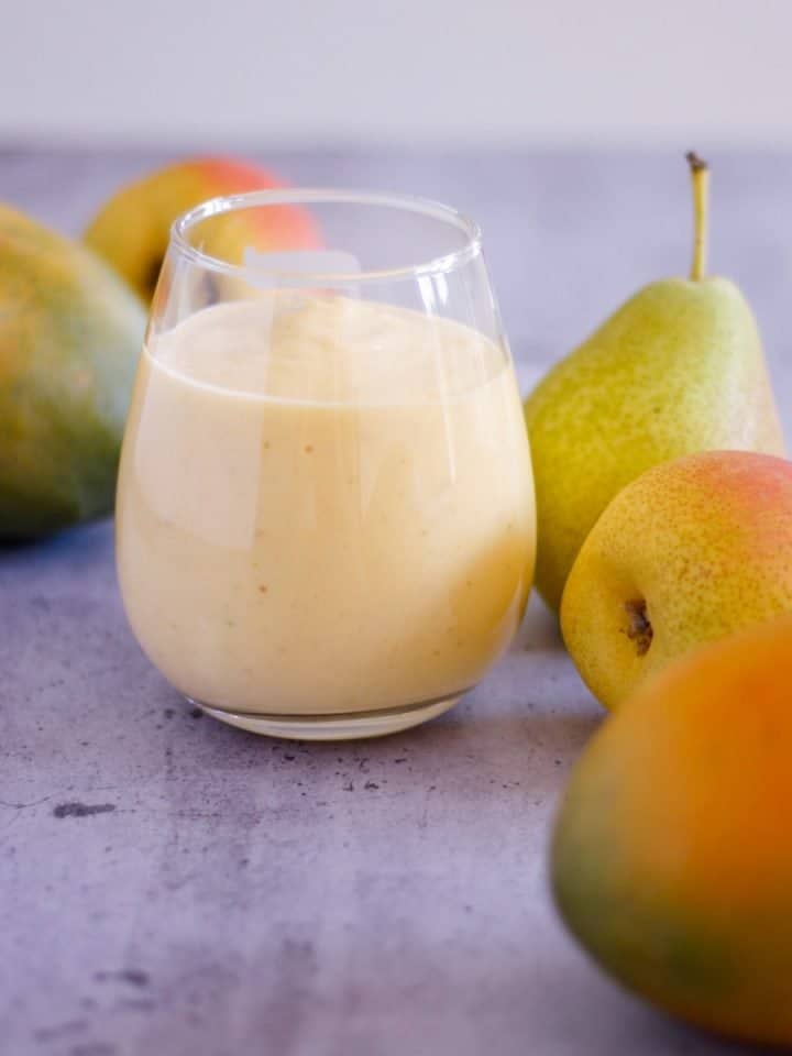 Glass of pear mango smoothie with mangoes and pears in background