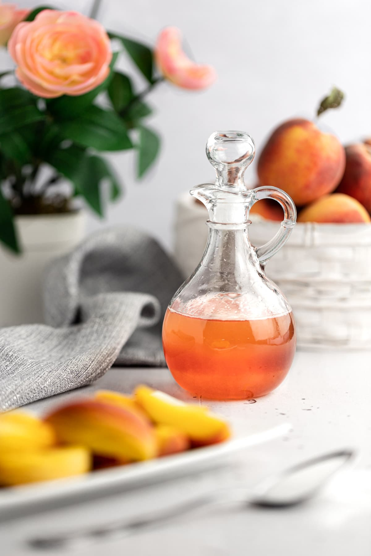 Peach syrup jar on a white table next to peach slices, a basket of peaches and pink flowers.