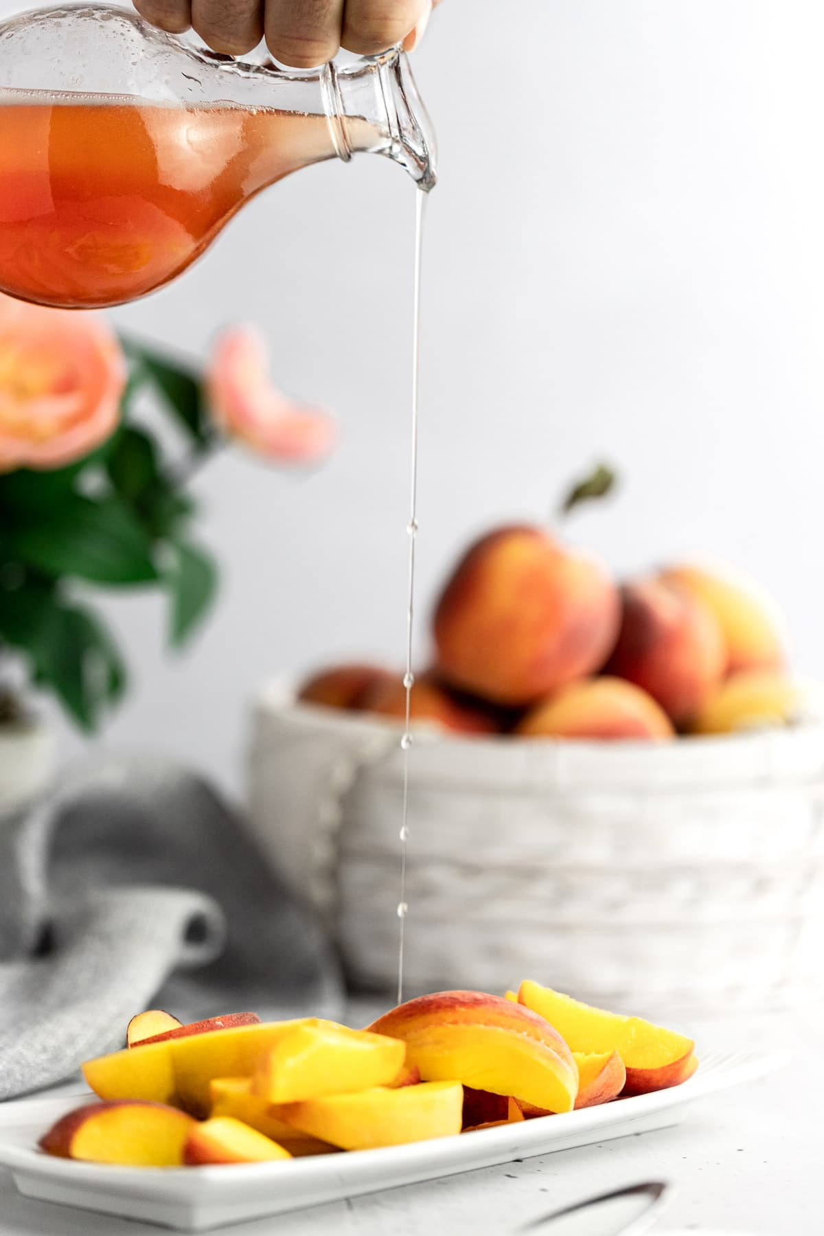 Syrup being poured over a plate of fresh peach slices, a grey napkin and basket of peaches in the background.