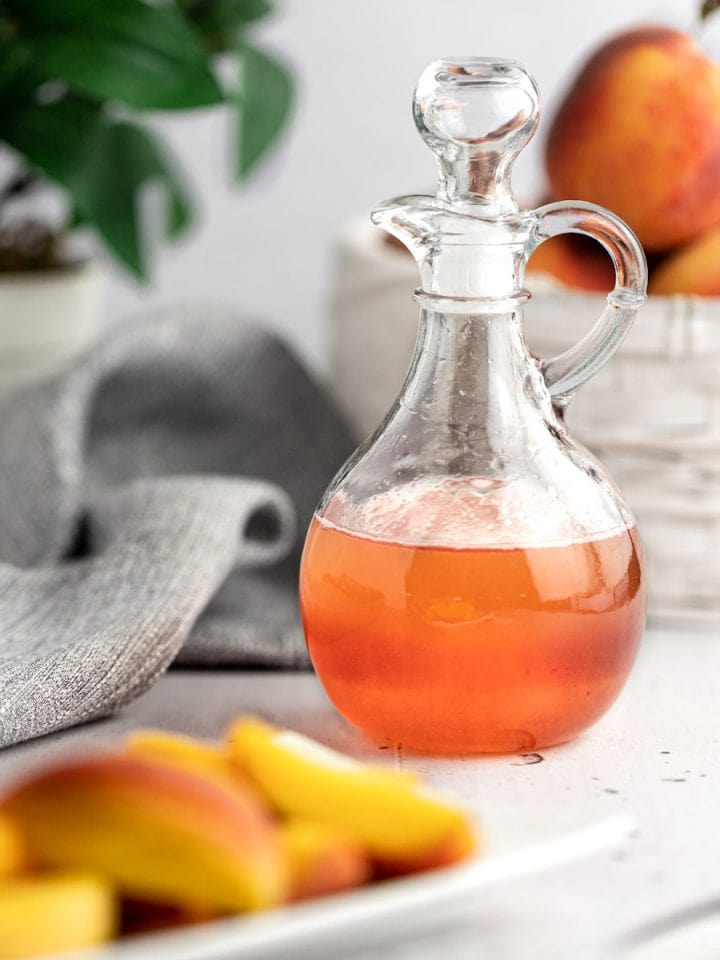 A jar of pink peach syrup on a table next to a plate of freshly sliced peaches, with pink flowers and a basket of peaches in the background.