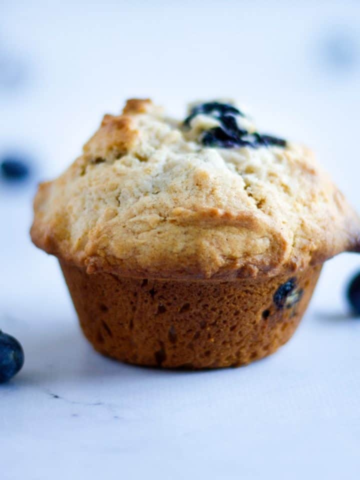 Up close side angle view of a pear and blueberry muffin with blueberries on the table beside