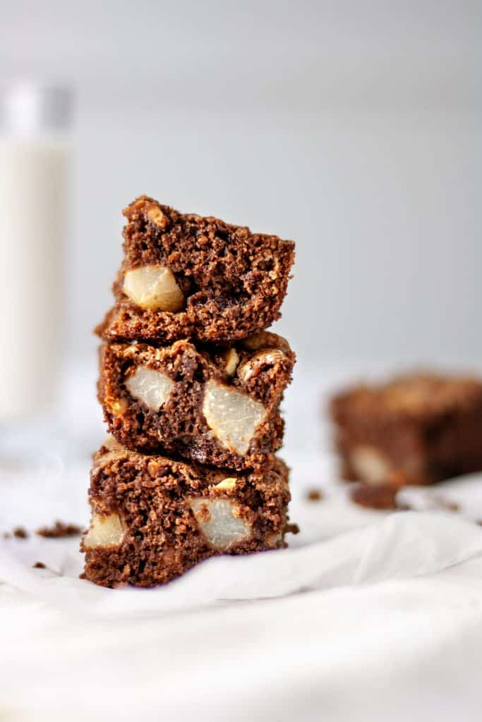 Three pear and hazelnut brownies stacked on top of each other, sitting on parchment paper
