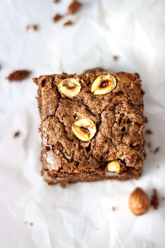 Overhead view of a pear and hazelnut brownies sitting on parchment paper
