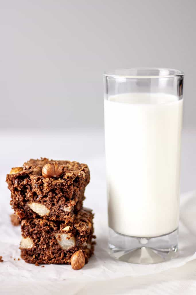 Two pear and hazelnut brownies stacked on top of each other next to a tall glass of milk