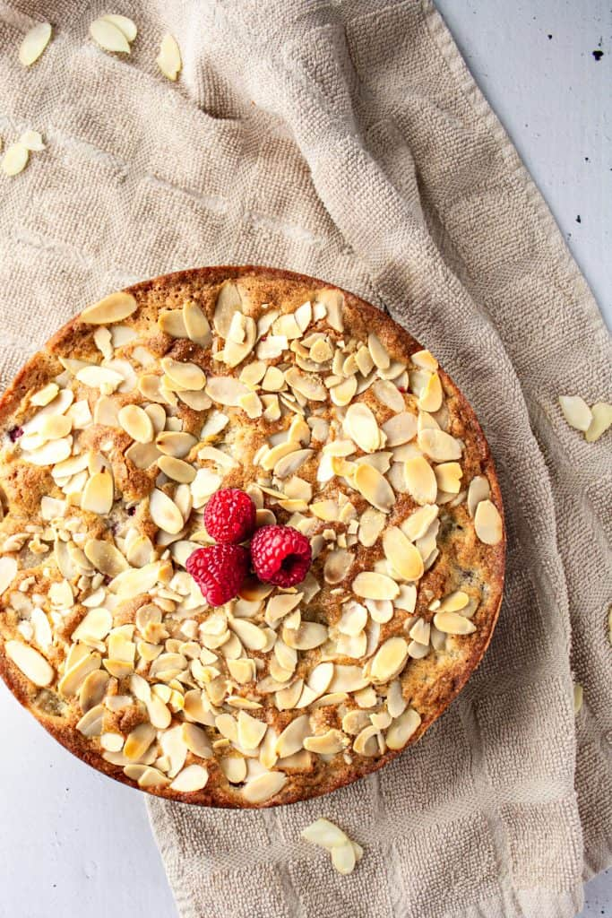 Overhead view of a whole pear raspberry cake wi the almonds and a few raspberries on top, sitting on a light brown hand towel