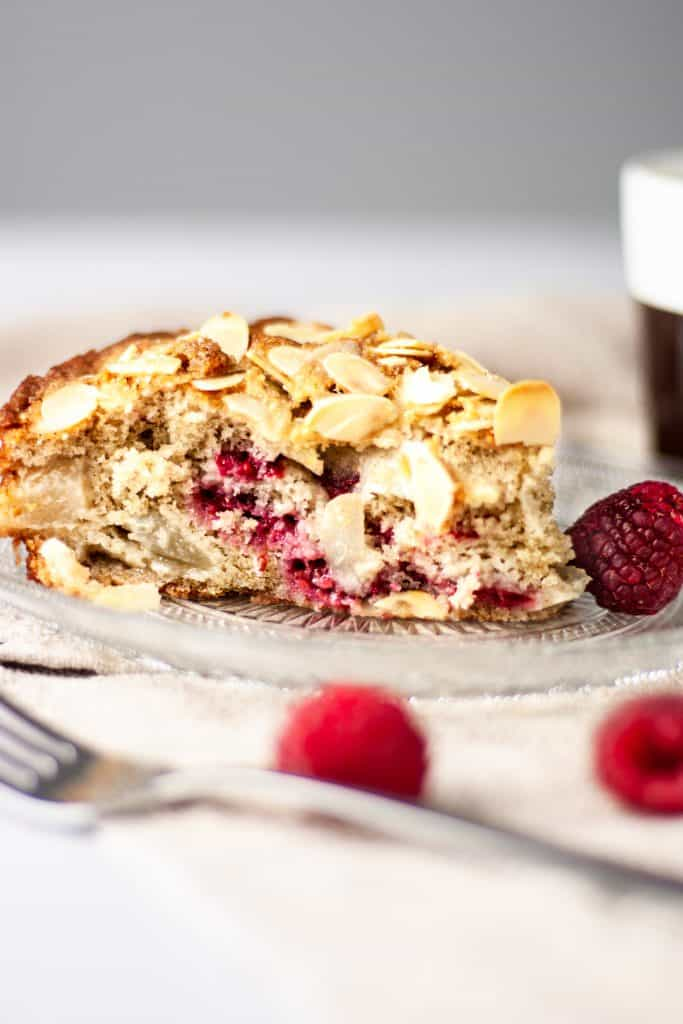 A side view of a slice of raspberry and pear cake beside a few raspberries and a cup of coffee