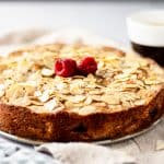 A fresh out of the oven pear and raspberry cake with sliced almonds and raspberries on top next to a cup of coffee.