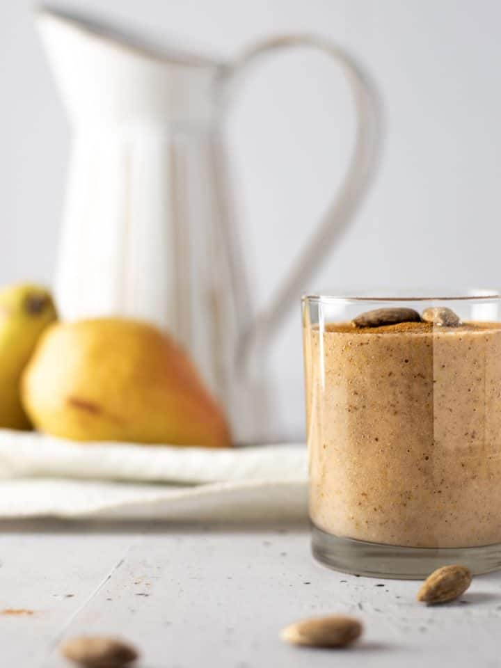 Side view of a glass of pear banana smoothie with three almonds in front and pears and a white jug in the background