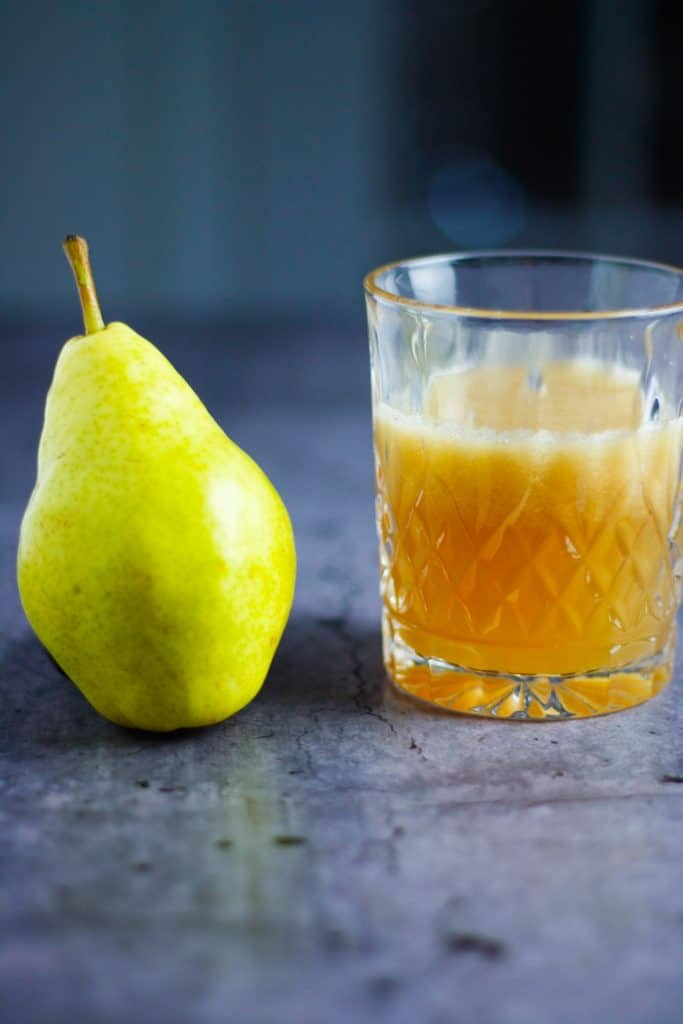 glass of pear bourbon cocktail lined up next to a pear
