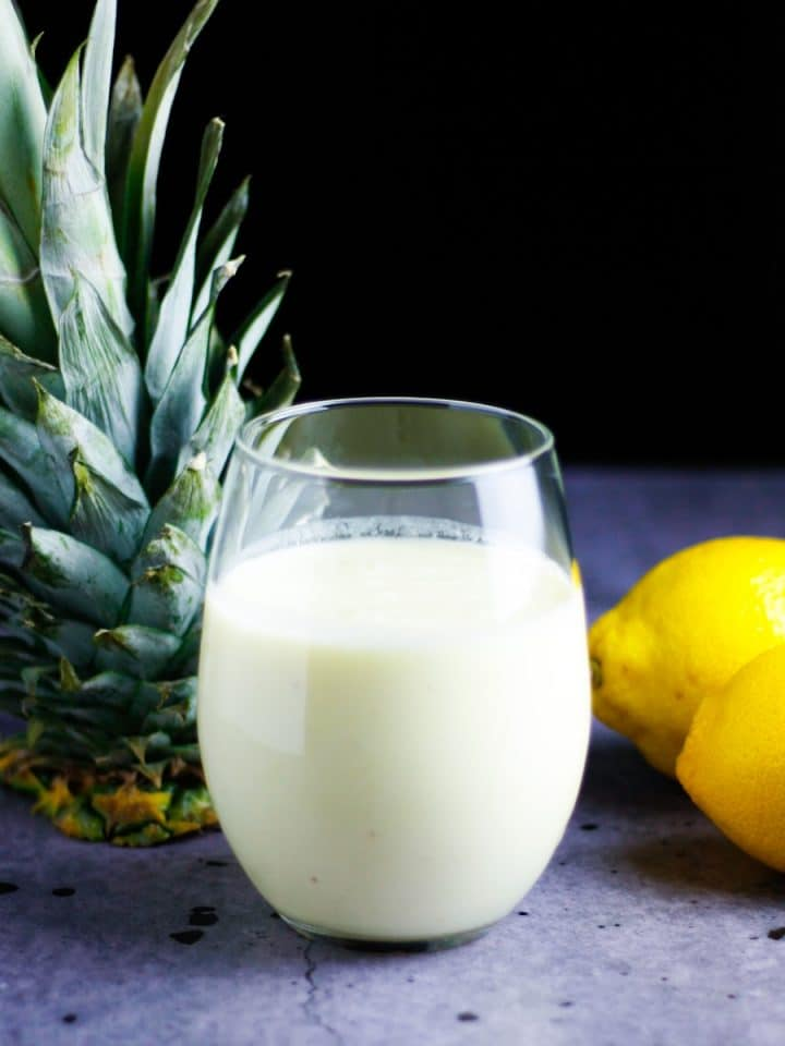 Glass of pineapple lemonade smoothie on the table with a pineapple top and lemons beside it
