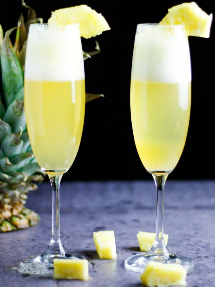 Two champagne glasses of pineapple mimosa on a table with a pineapple in the background