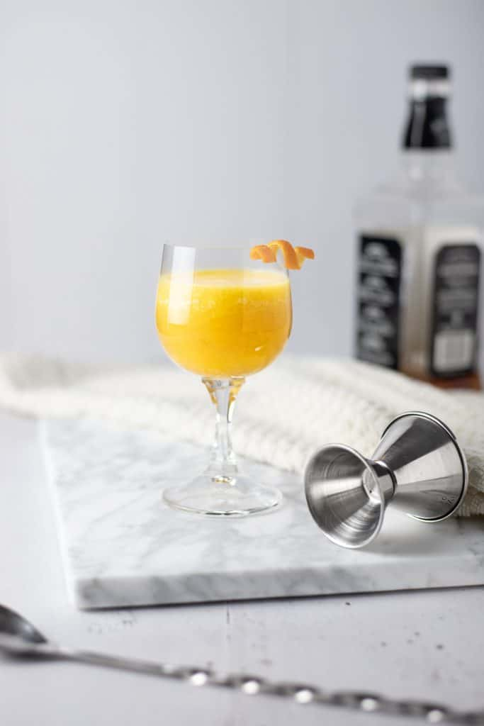 A pineapple old fashioned on a marble cutting board with a spoon in front and jigger and whiskey bottle in the background