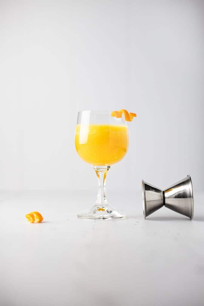 A pineapple old fashioned cocktail with an orange peel garnish next to a toppled jigger and extra orange garnish