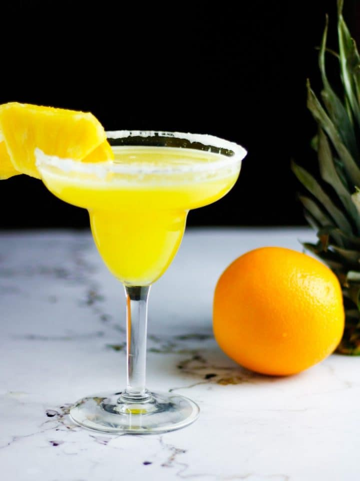 Glass of pineapple orange margarita on a table with an orange and pineapple in the background