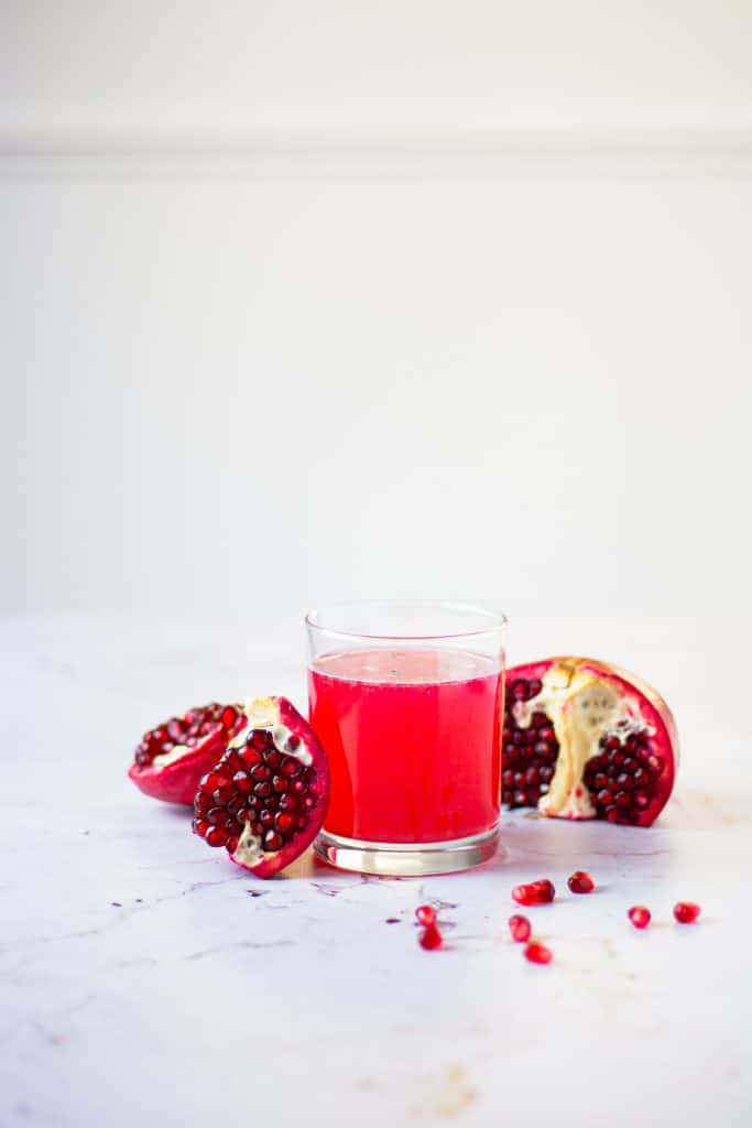 Clear class filled with red pomegranate gin fizz with an opened pomegranate beside it on the table