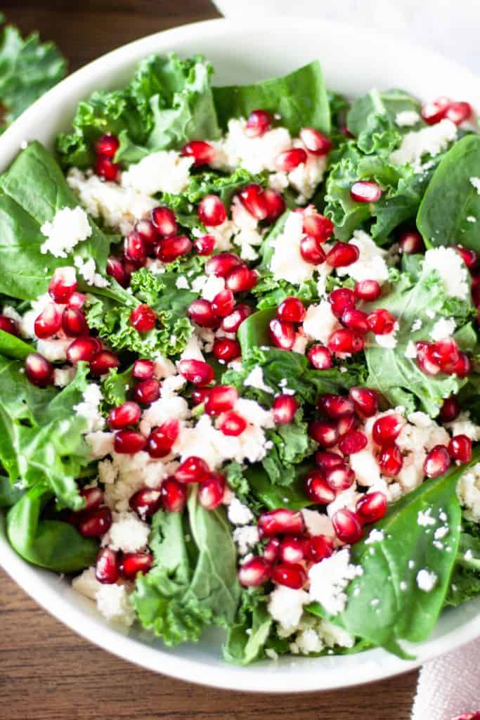 Up close overhead view of pomegranate kale salad in a white bowl