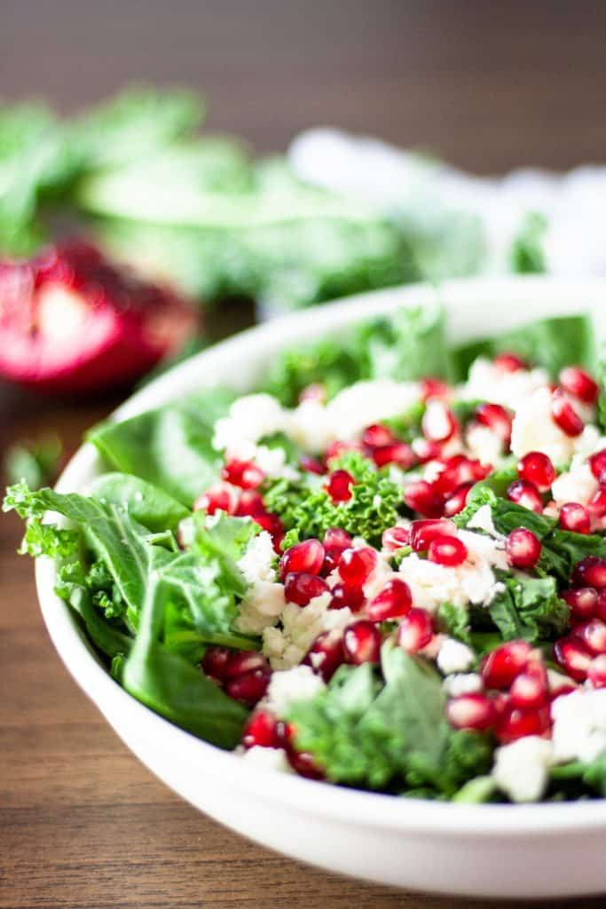 Side angle view of pomegranate feta salad on a wooden table