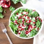 Overhead view of a bowl of pomegranate kale and feta salad on a wooden table with a fork beside it