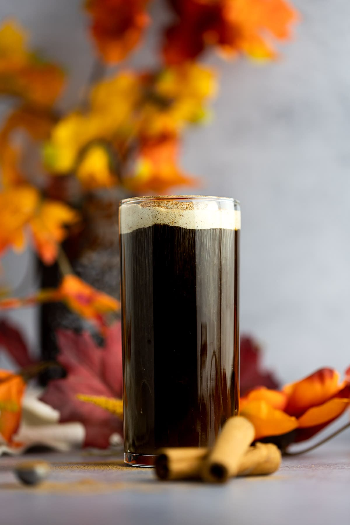A tall glass of coffee topped with pumpkin foam, with cinnamon sticks beside it and leaves in the background.