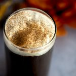 Pumpkin cold foam sprinkled with pumpkin spice, sitting on top of a glass of black coffee.