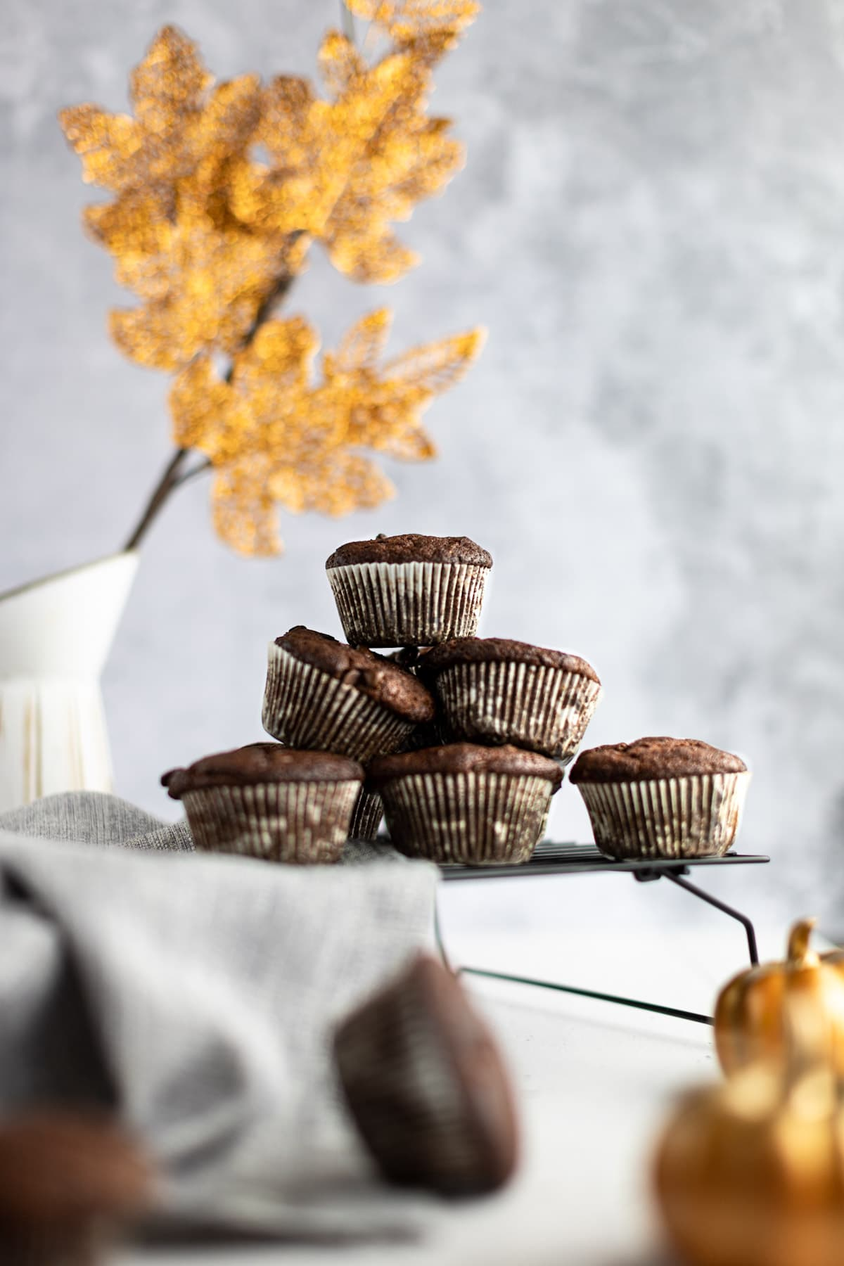 A pyramid of pumpkin protein muffins sitting on a wire cooling rack, with golden shiny leaves in the background.