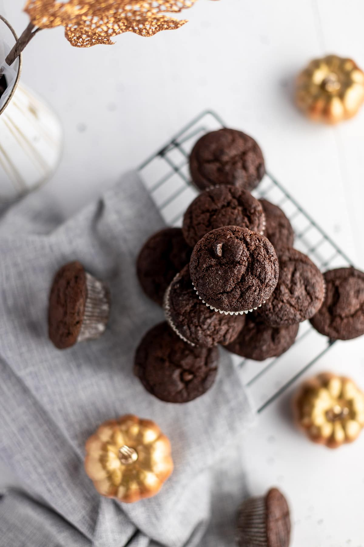 Overhead photo of a stack of chocolate pumpkin muffins, on a grey napkin, surrounded by decorative gold pumpkins.