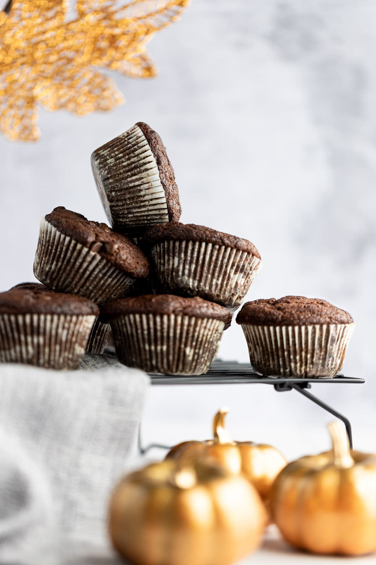 Up close view of a stack of protein muffins on a black wire rack, with a stack of golden pumpkins in front.