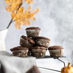 A stack of pumpkin protein muffins on a black wire rack, with a vase of golden leaves in the background.
