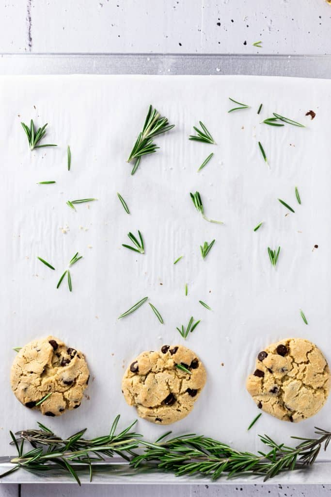 Overhead view of 3 rosemary cookies at the bottom of a cookie sheet with fresh rosemary scatter above like rain coming down