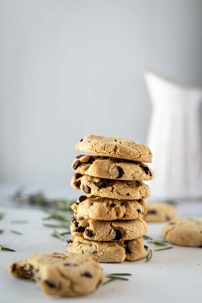 A stack of rosemary chocolate chip cookies with a half eaten cookie in the foreground and a white vase in the background