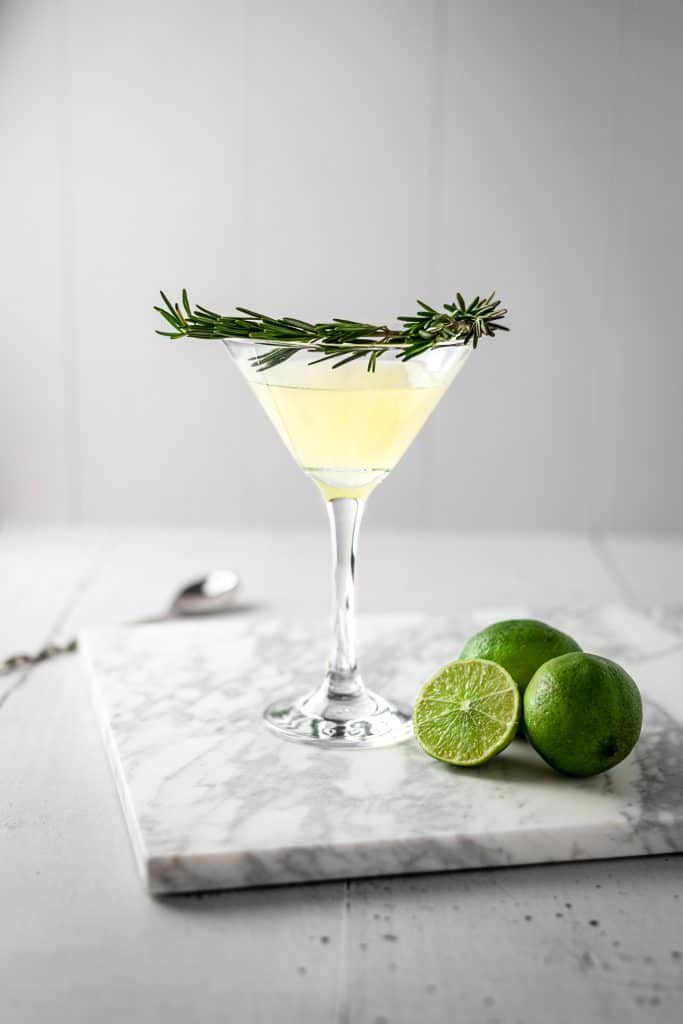 Rosemary gimlet with a branch of fresh rosemary as garnish around the glass, three lines sitting on the marble table beside the cocktail