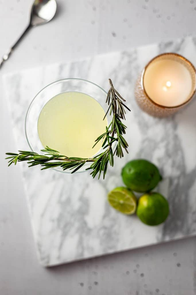 Overhead view of gimlet with rosemary garnish, 3 limes and a lit candle on a white marble board