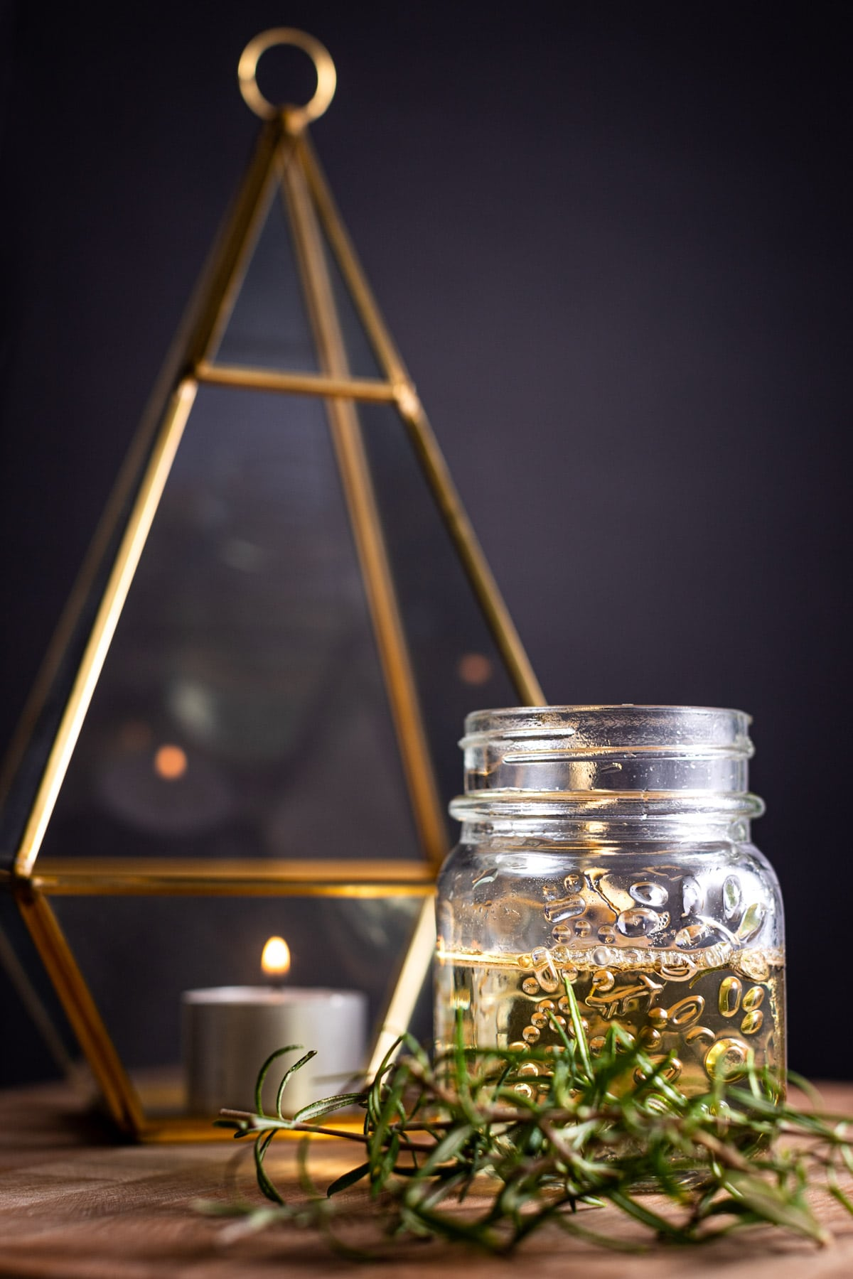Jar of rosemary simple syrup, on a wooden board, next to a candle, gold votive and fresh rosemary on a black background.