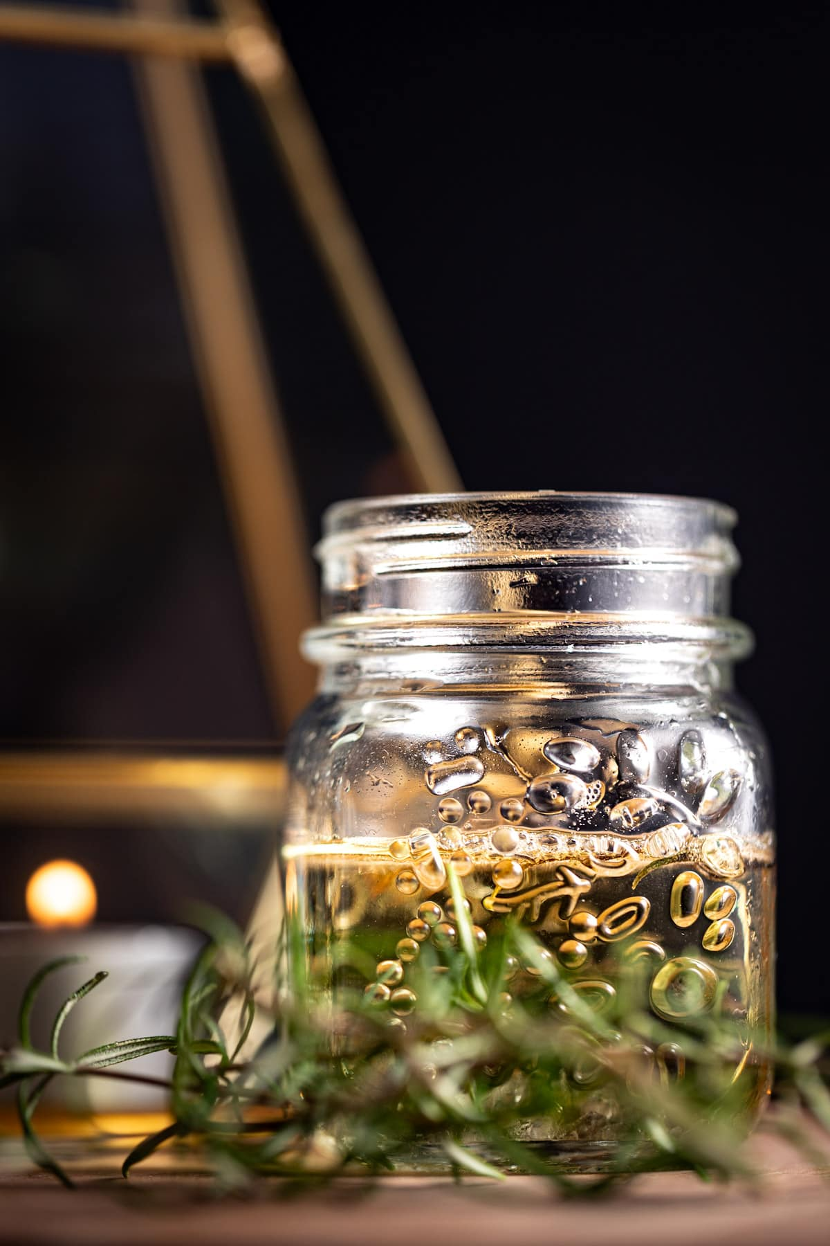 Syrup in a small glass jar, with fresh rosemary herbs in front of it, on a black background.