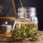A small glass jar filled with rosemary syrup, with fresh rosemary in front and a candle in the background.