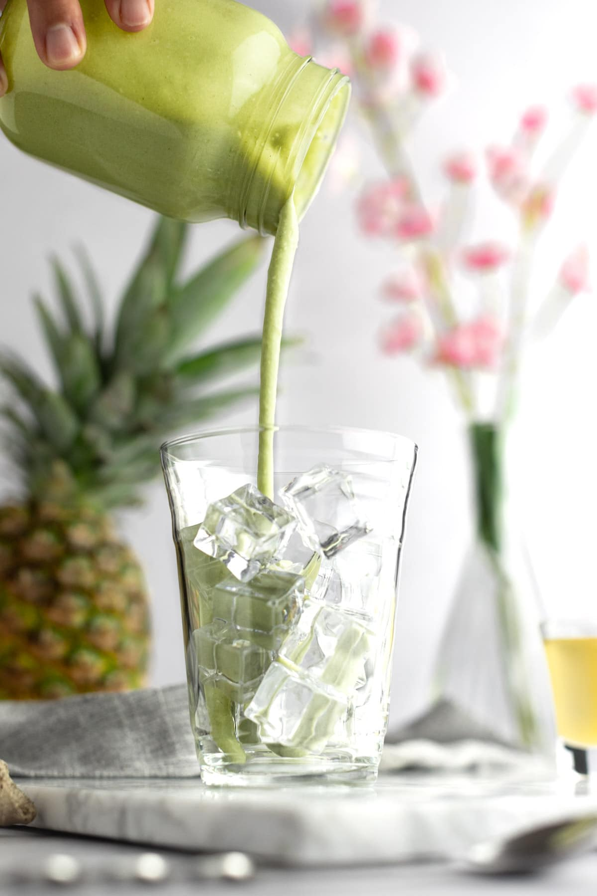 A hand pouring the matcha drink into a glass filled with ice cubes, with a pineapple in the background.