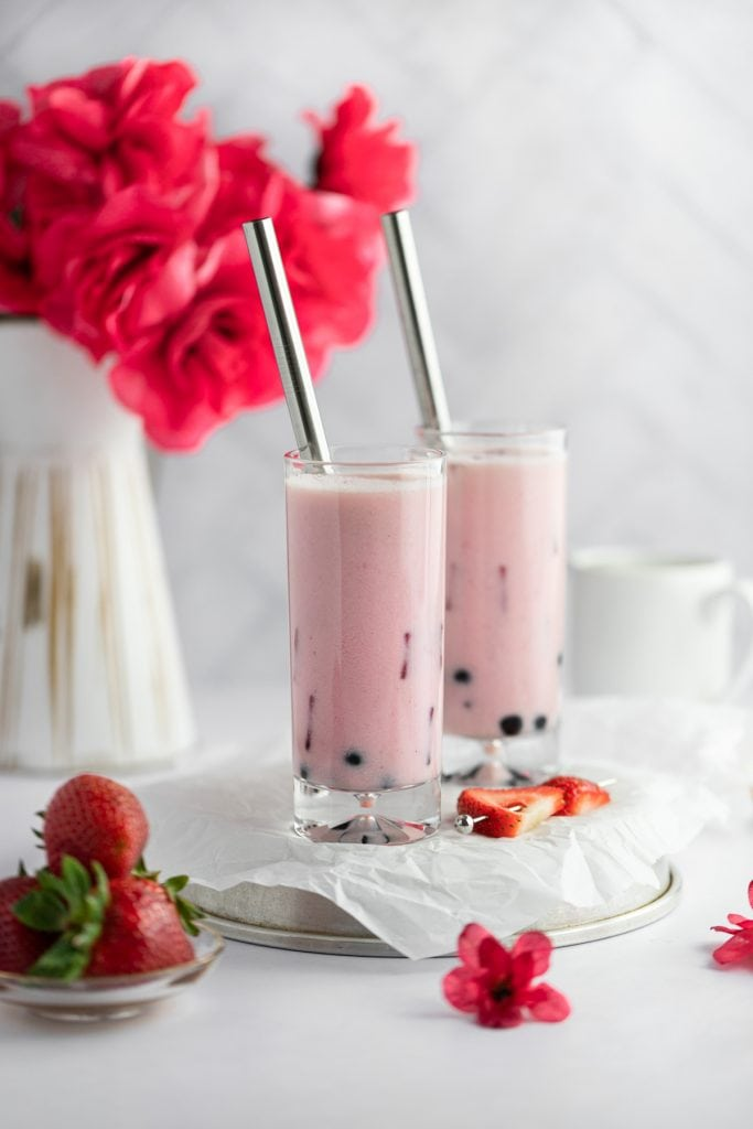 Two tall glasses of strawberry milk tea with a vase of red roses in the background and a plate of strawberries in the foreground.