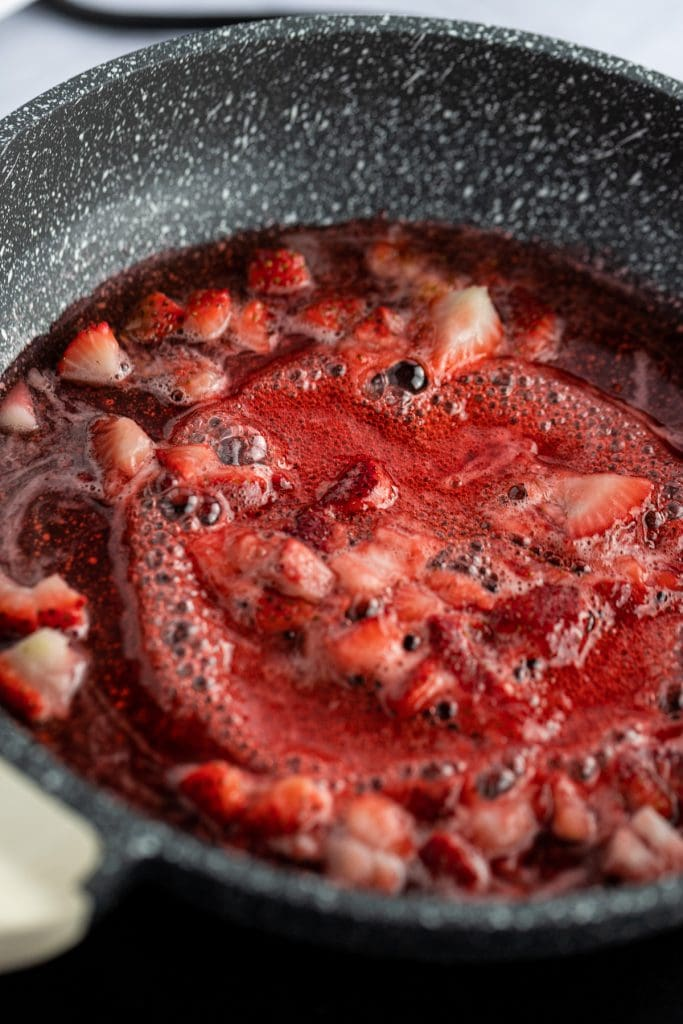 Close up photo of red strawberry syrup simmering on a saucepan.