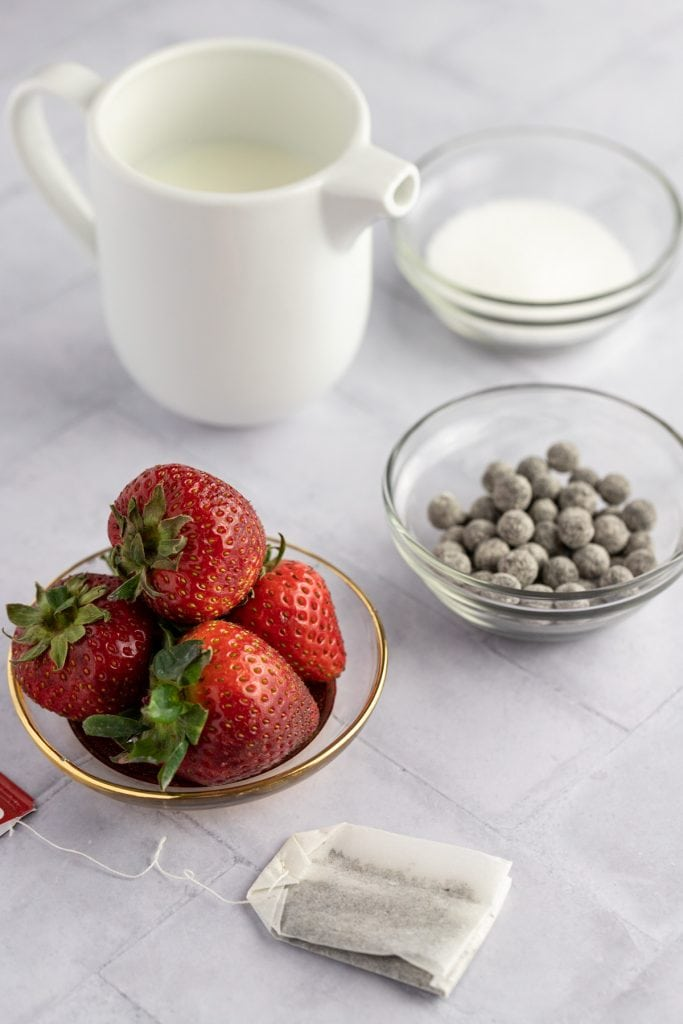 Ingredients shot of fresh strawberries, a tea bag, uncooked boba, milk and sugar.