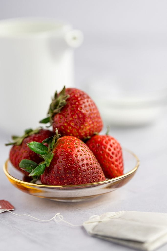 Up close photo of a small pile of fresh strawberries sitting on a small glass and gold plate with a tea bag in front.