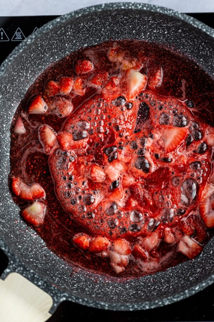 Overhead photo of strawberry syrup with chunks of strawberries simmering in a pan.