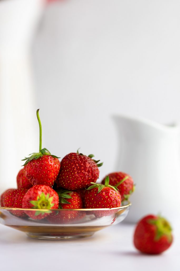 A small glass dish holding a pile of fresh strawberries.