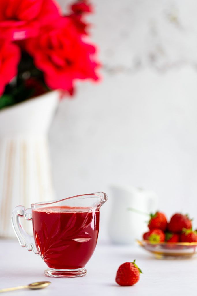 A small glass container filled with red strawberry simple syrup, a pile of strawberries in the background and a small gold spoon in the foreground.