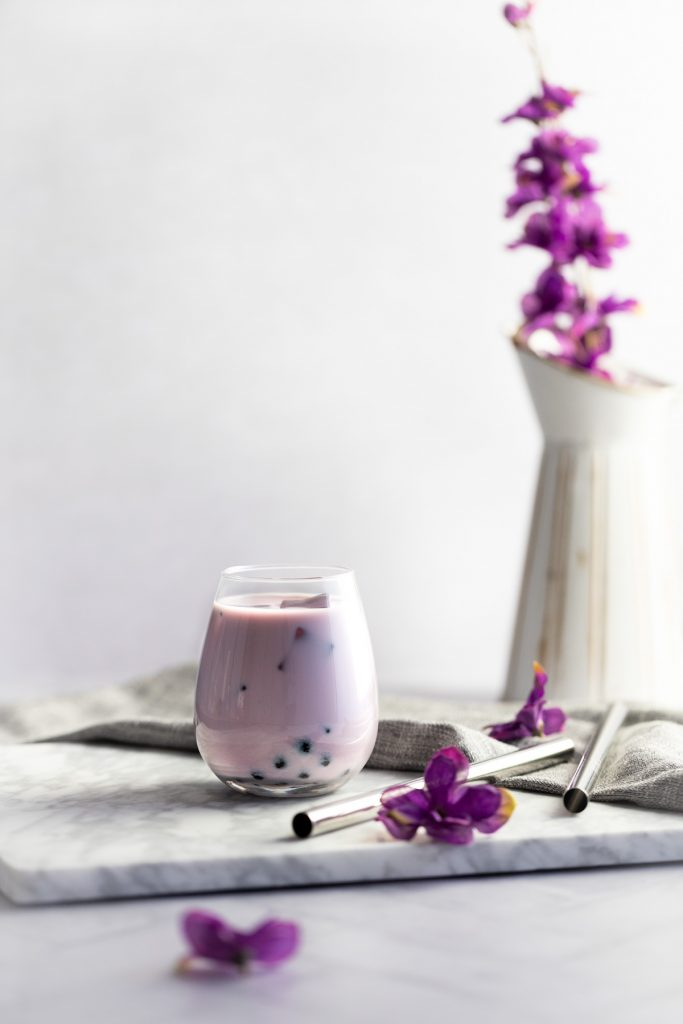 Glass of taro milk tea on a white marble board with a grey napkin, bubble tea straws and a vase of purple flowers in the background.